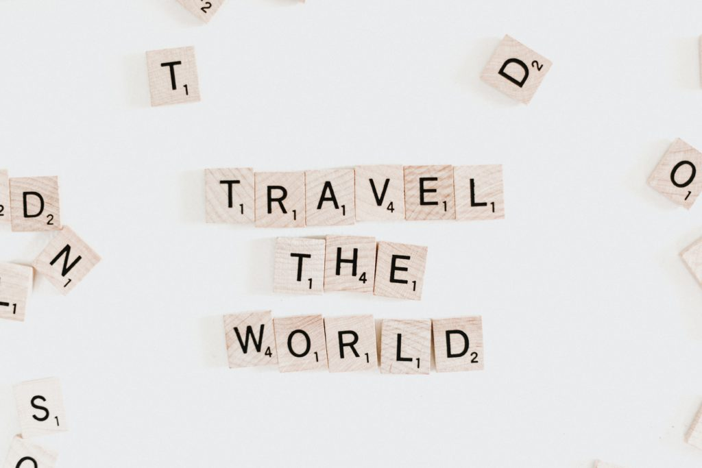 scrabble pieces spelling out 'travel the world'
